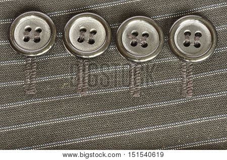 Four round buttons on a striped jacket sleeve.