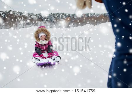 childhood, sledding, leisure, season and people concept - parent carrying happy little kid on sled in winter