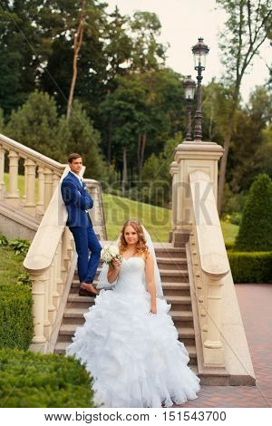 Newlyweds pose on the stairs on a wedding day