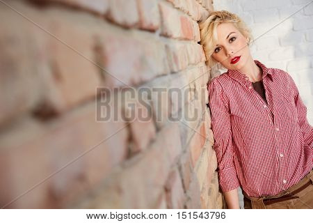 Attractive young blonde woman posing by brick wall.