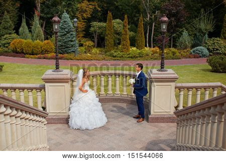 Newlyweds pose by the stairs on a wedding day