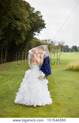 Newlyweds kiss in the park on a warm sunny day