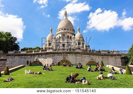 Paris France - July 06 2016: Tourists sitting on the grass near Basilica Sacre Coeur on Montmartre hill in the sunny summer day.