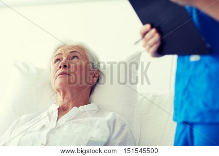 medicine, age, health care and people concept - senior woman patient and doctor or nurse with clipboard at hospital ward