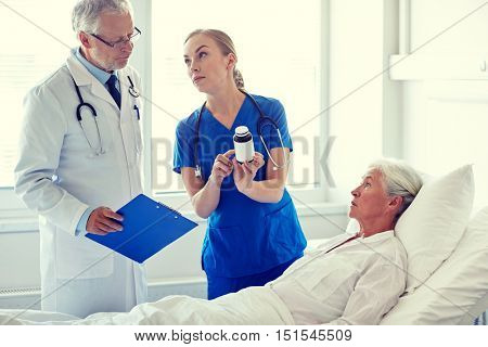 medicine, age, health care and people concept - doctor and nurse with medicine and senior woman at hospital ward