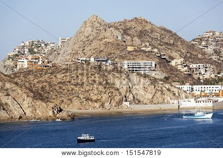 The tender boat is leaving Cabo San Lucas resort town (Mexico).