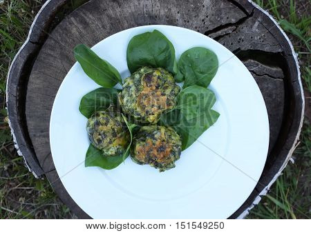 Spinach pancakes with green spinach leaves on a tree stump outdoors