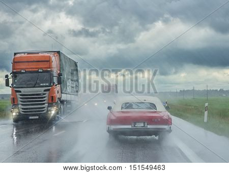 Modern truck and an old cabriolet on the road in the rain