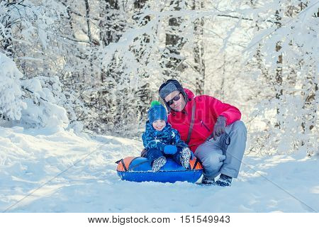 Happy Toddler boy with dad in the snowy forest outdoors