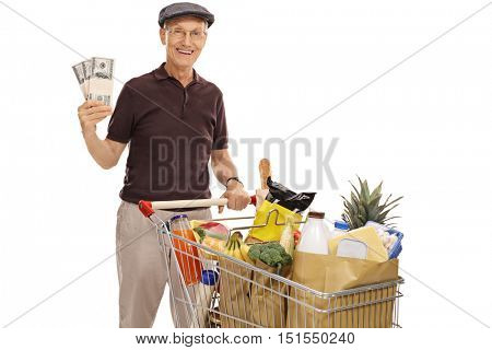 Happy mature man posing with a shopping cart full of groceries and bundles of money isolated on white background