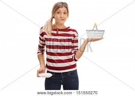 Broke woman showing her empty pocket and holding a small empty shopping basket isolated on white background