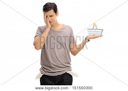 Depressed man posing with a small empty shopping basket and holding his head in disbelief isolated on white background