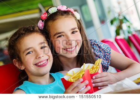 two happy girls in fast food restaurant eating french fries and smile
