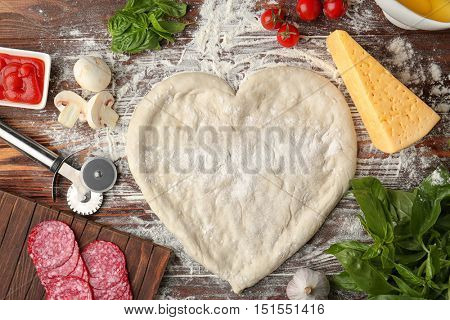 Pizza dough in heart shape with ingredients on table