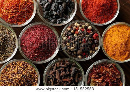 Various spices in glass bowls, close up