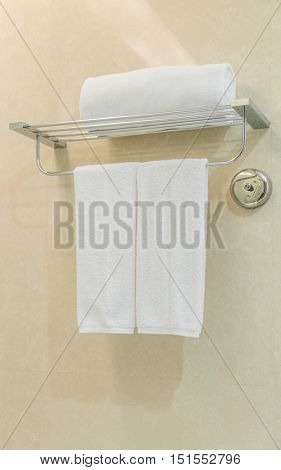 Clean white towel on a hanger prepared in bathroom