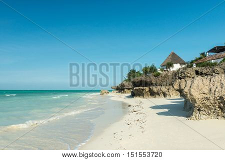 beautiful colorful seascape with thatched houses on Zanzibar beach and horizon