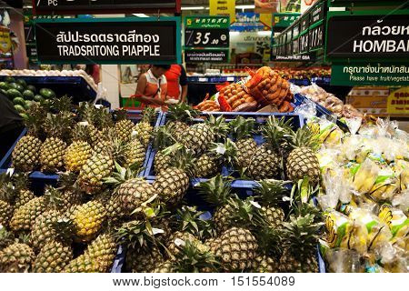 Pattaya Thailand - March 23 2016: Asian supermarket shelf: pile of pineapples bananas and other fruits. Thai and English market sign: wrong spelling