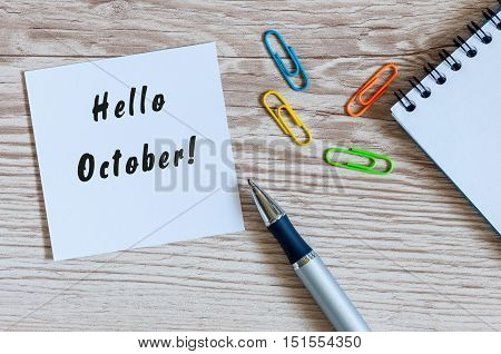 Paper with words HELLO OCTOBER and office suplies lying on wooden table, home or job workplace. Autumn concept.