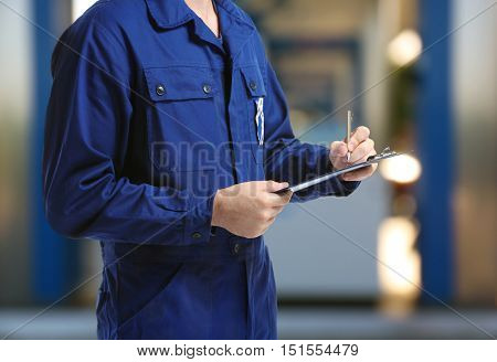 Mechanic in uniform with a clipboard and pen on gas station blurred background