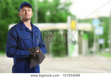 Young mechanic in uniform with rag standing on blurred petrol station