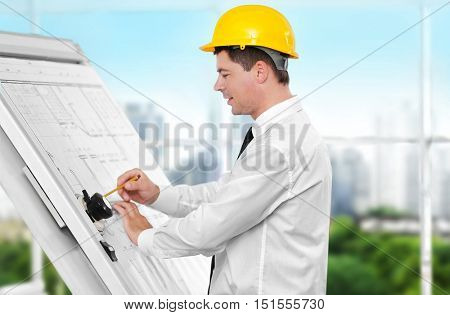Young creative male engineer making project on drawing board