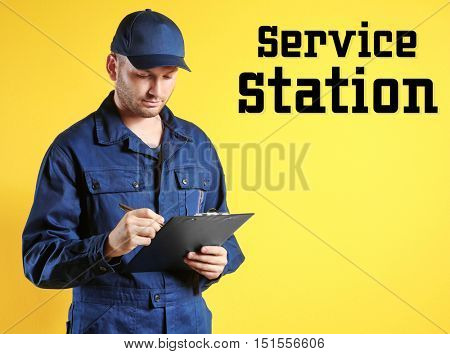 Young mechanic in uniform with a clipboard standing on a yellow background