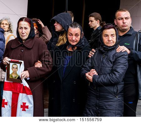 Uzhhorod Ukraine - 2016. October 12: Relatives of ukrainian soldier who died of his wounds in the ATO zone kept a portrait and the Georgian flag during a farewell ceremony. The coffin with the body of the deceased Ukrainian heroic warrior honorably carrie