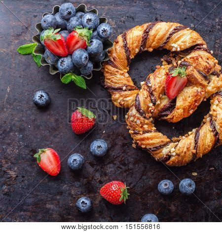 Homemade sweet pretzel with chocolate, crunchy almonds, berries, traditional german bavarian treat on a black rusty table. Selective focus, top view overhead flat lay