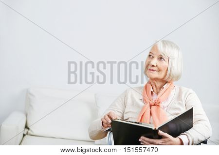 Senior woman in a wheelchair with book looking pensive