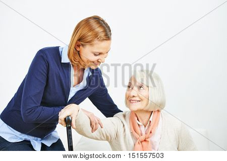 Caregiver helping senior woman with cane getting up from a sofa