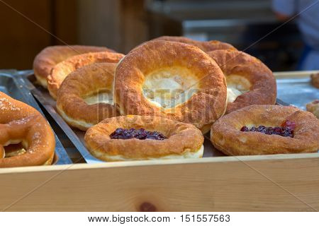 Closeup tray of fresh Bauernkrapfen, traditional German fried dough pastry eaten with cranberry jam