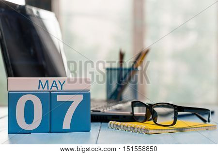 May 7th. Day 7 of month, calendar on business office background, workplace with laptop and glasses. Spring time, empty space for text.
