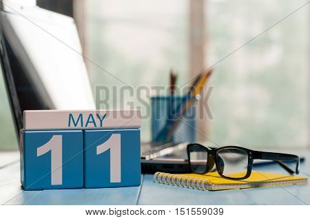 May 11th. Day 11 of month, calendar on business office background, workplace with laptop and glasses. Spring time, empty space for text.