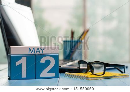 May 12th. Day 12 of month, calendar on business office background, workplace with laptop and glasses. Spring time, empty space for text.