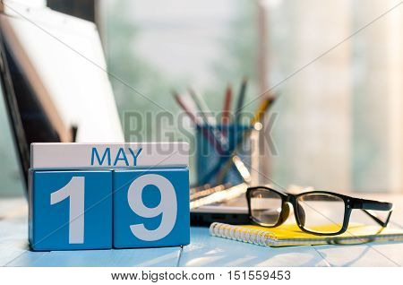 May 19th. Day 19 of month, calendar on business office background, workplace with laptop and glasses. Spring time, empty space for text.