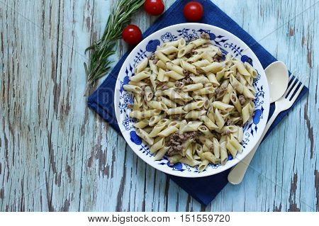 penne pasta with meat and herbs on a wooden table