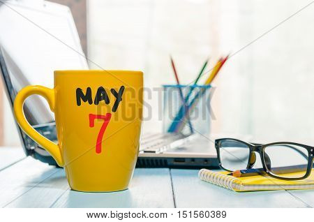 May 7th. Day 7 of month, calendar on morning coffee cup, business office background, workplace with laptop and glasses. Spring time, empty space for text.