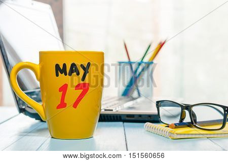 May 17th. Day 17 of month, calendar on morning coffee cup, business office background, workplace with laptop and glasses. Spring time, empty space for text.