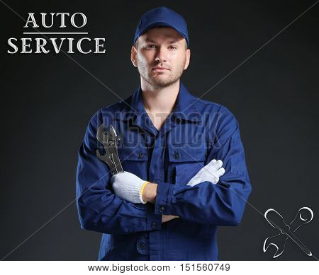 Young mechanic in uniform and gloves with a wrench standing on a black background