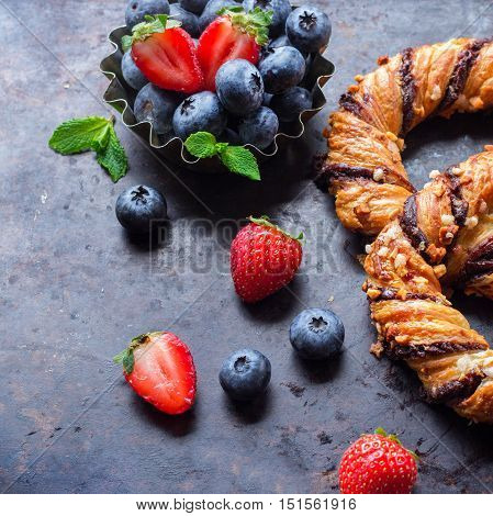 Homemade sweet pretzel with chocolate, crunchy almonds, berries, traditional german bavarian treat on a black rusty table. Selective focus