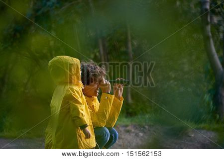 Mom with her daughter looking into the distance through a spyglass