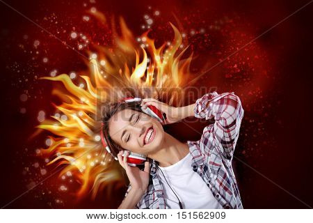 Young woman listening to music in headphones with burning hair on red background.