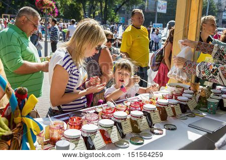 Zaporizhia/Ukraine- September  17, 2016: Family festival of homemade pickled canned vegetables and preserves. Mother and daughter  tasting jams and confitur near the stand with different sorts of sweet preserves in glass jars.