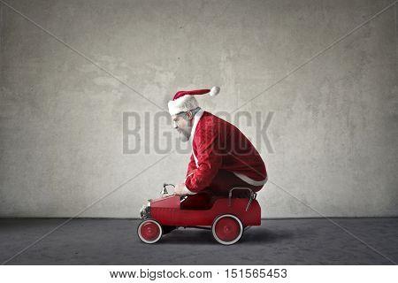 Santa Claus driving a toy car