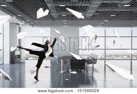 Dancing businesswoman in office room . Mixed media