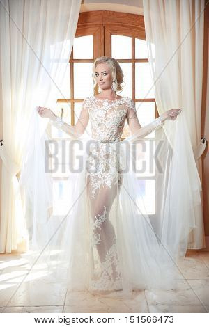 Fashion Bride Model In Wedding Dress Posing In Front Of Curtains Window, Indoor Bridal Portrait. Lux