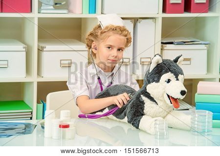 Cute little girl playing a doctor at home. Different occupations. Children's Health, Pediatrics.