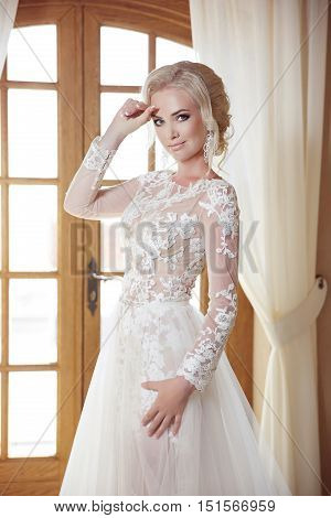 Portrait Of Beautiful Bride In Wedding Dress Against A Window, Indoors. Blonde Young Woman With Make