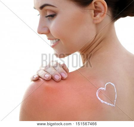 Woman with sun protective lotion in heart shape on shoulder